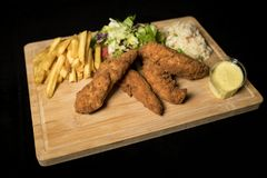 Chicken Goujons served with rice, salad and french fries on wood royalty free stock photo