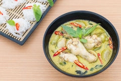Chicken green curry with Rice vermicelli. On wooden background Stock Image