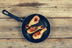 Chicken grilled legs. Fried chicken legs in a frying pan on a wooden table Royalty Free Stock Image
