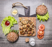 Chicken grilled with mustard sauce with ingredients for homemade burger, vegetables and spices wooden rustic background top vie Royalty Free Stock Photos