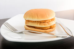 Chicken hamburger in white plate with knife and fork, on top tab Royalty Free Stock Photos