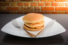 Chicken hamburger in white plate with knife and fork, on top tab Stock Image