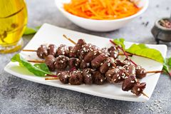 Chicken hearts in spicy sauce and carrot salad. Healthy food stock photo