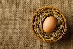 Chicken or hen egg on straw in wicker basket on sackcloth royalty free stock photo