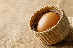 Chicken or hen egg in wicker basket on sackcloth stock images