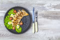 Chicken with honey and mustard souse, lettuce, quail eggs, cherry tomatoes royalty free stock photography