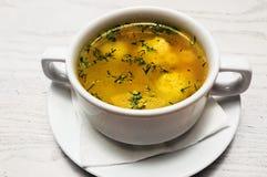 Chicken hot broth in white soup tureen. Studio Photo Stock Photo