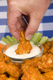 Chicken hot wings. A dish of chicken hot wings, celery and carrots with dipping sauce attracts a man who dips a wing into some tasty ranch sauce at a picnic royalty free stock images