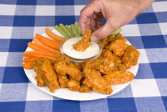 Chicken hot wings. A dish of chicken hot wings, celery and carrots with dipping sauce attracts a man who dips a wing into some tasty ranch sauce at a picnic Royalty Free Stock Photo