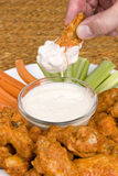 Chicken hot wings and dipping sauce. A dish of chicken hot wings, celery and carrots with dipping sauce attracts a man who dips a wing into some tasty ranch Stock Photography