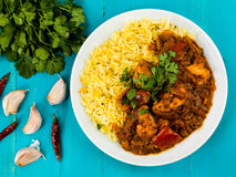 Chicken Jalfrezi Curry With Basmati Spiced Rice. Against a Blue Wooden Background Royalty Free Stock Photography
