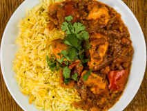 Chicken Jalfrezi Curry With Basmati Spiced Rice. Against a Dark Oak Wooden Background Stock Photo