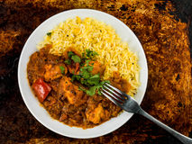 Chicken Jalfrezi Curry With Basmati Spiced Rice. Against a Distressed Oven or Baking Tray Stock Image