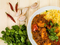Chicken Jalfrezi Curry With Basmati Spiced Rice. Against a Light Pine Wooden Background Royalty Free Stock Images