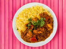 Chicken Jalfrezi Curry With Basmati Spiced Rice. Against a Pink Wooden Background Stock Images