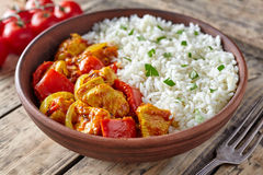Chicken jalfrezi healthy traditional Indian curry spicy fried meat with vegetables. And basmati rice food in clay plate on vintage table background stock photography