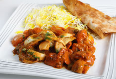 Chicken jalfrezi plate. Chicken jalfrezi curry on a plate with pilau rice and a piece of naan bread Stock Image