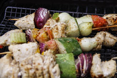 Chicken Kabobs on the Grill - Closeup. Along with fresh vegetables from the garden, this marinated chicken is threaded onto skewers and grilled. Focus is Royalty Free Stock Photography