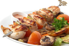 Chicken kebab closeup. Chicken kebab with grilled vegetables on white plate, selective focus Stock Photo