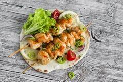 Chicken kebab and fresh vegetables on a homemade tortilla Stock Photos