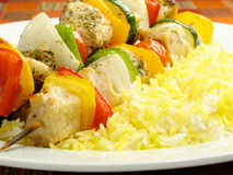 Chicken Kebab and Saffron Rice. Seasoned chicken kebabs with bell peppers, onions, zucchini, and cherry tomatoes. Accompanied by a bed of saffron flavored royalty free stock image