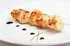Chicken kebab on skewer in white plate. With sauce and onion royalty free stock photo