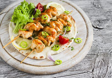 Chicken kebabs and fresh vegetable salad on a homemade tortilla Royalty Free Stock Image