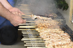 Chicken kebabs on the grill and human hands Royalty Free Stock Image
