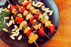 Chicken kebabs with pepper and zucchini on black plate. On wooden table Stock Photo