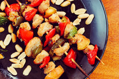 Chicken kebabs with pepper and zucchini on black plate. On wooden table Stock Images