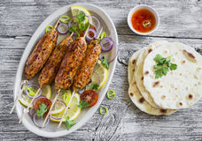 Chicken kebabs on wooden skewers on an oval plate and homemade tortilla Stock Photography