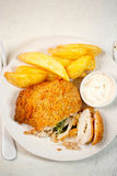 Chicken kiev with basil pesto, potato chips and mayo dip. On white plate Royalty Free Stock Photo