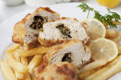 Chicken kiev with french fries. Breaded and stuffed chicken kiev with french fries and lemon Stock Photo