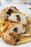 Chicken kiev with french fries. Breaded and stuffed chicken kiev with french fries and lemon Stock Photos