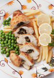 Chicken kiev with french fries and peas. Chicken kiev with french fries and green peas Royalty Free Stock Image