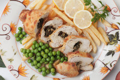 Chicken kiev with french fries and peas Stock Photo
