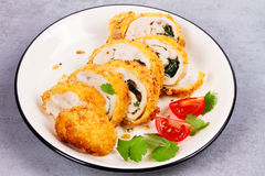 Chicken Kiev garnished with tomato and cilantro. Breaded chicken breast stuffed with herbs and butter on white plate. Royalty Free Stock Photography