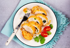 Chicken Kiev garnished with tomato and cilantro. Breaded chicken breast stuffed with herbs and butter on white plate. View from above, top studio shot Stock Image