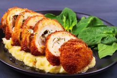 Chicken Kiev on mashed potato with spinach. Stock Photo