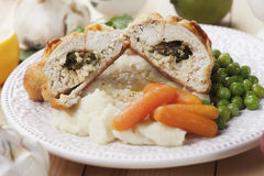 Chicken kiev with vegetables. Breaded and stuffed chicken kiev with green peas and carrot Stock Image