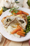 Chicken kiev with vegetables. Breaded and stuffed chicken kiev with green peas and carrot Stock Photography