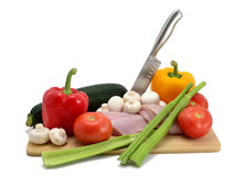 Chicken, knife and vegetables Stock Image