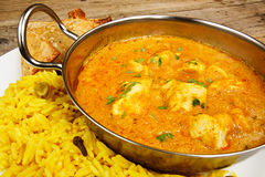 Chicken korma in balti dish with rice. Chicken Korma a popular sweet indian curry dish of coconut and cream sauce served in a dish on a plate with pilaf rice and Royalty Free Stock Photography