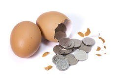 A chicken lays an egg and there is money inside Stock Photo