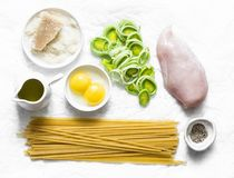 Chicken, leek, linguine pasta, parmesan cheese, eggs yolks, olive oil - ingredients for cooking carbonara pasta on a light stock images