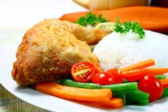 Chicken leg. Crispy fried chicken with veggies and rice stock image