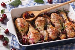 Chicken leg with cherry in dish for baking. Horizontal Royalty Free Stock Image