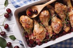 Chicken leg with cherry in dish for baking. Horizontal top view Royalty Free Stock Photo