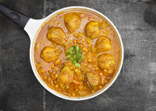 Chicken leg with chickpeas and curry sauce in white pan Royalty Free Stock Photo