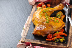 Chicken leg. Closeup shot of baked chicken leg with thyme and vegetables on slate Stock Photos